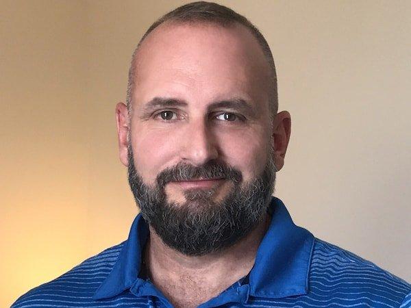 Kurt Robbins portrait in royal blue polo shirt